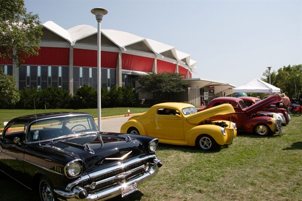What types of cars appear in a Goodguys custom car show?